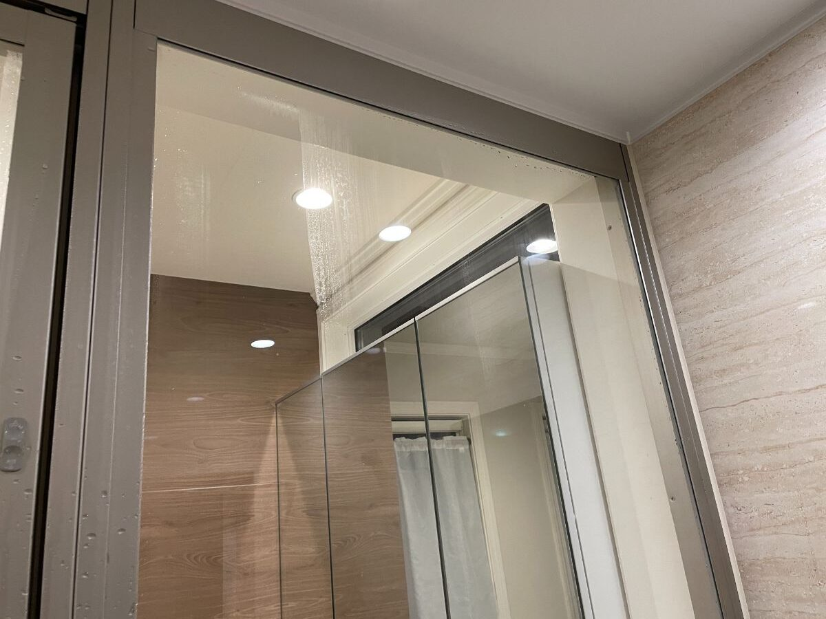 お風呂のガラス窓にスキージーをする画像